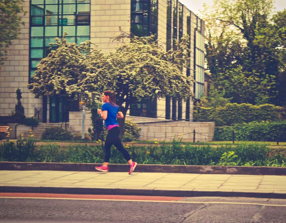 Läuferin auf dem Bürgersteig vor einem Gebäude