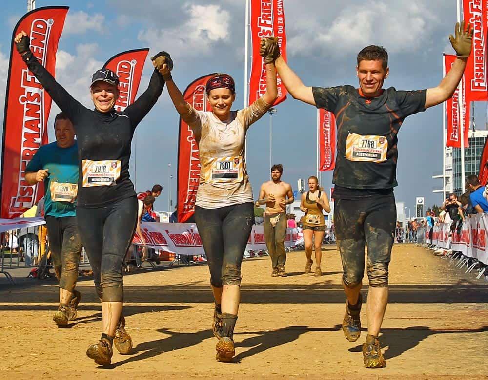 Läuferin Lola mit zwei Freunden beim Zieleinlauf vom Fishermans Friend Strongman Run