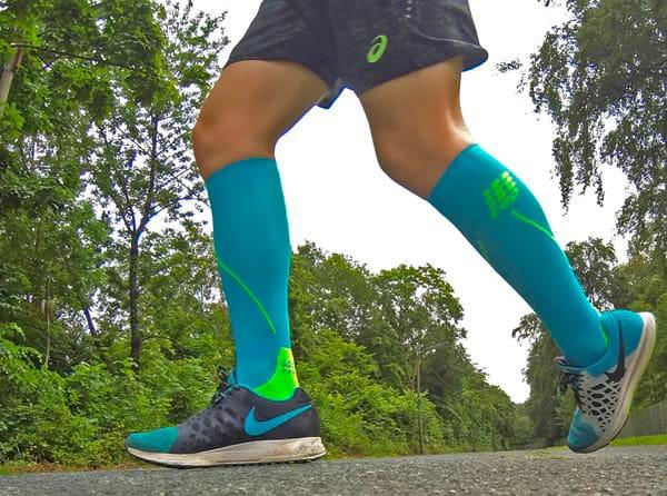Beine eines Läufers auf einer Straße mit Kompressionsstrümpfen