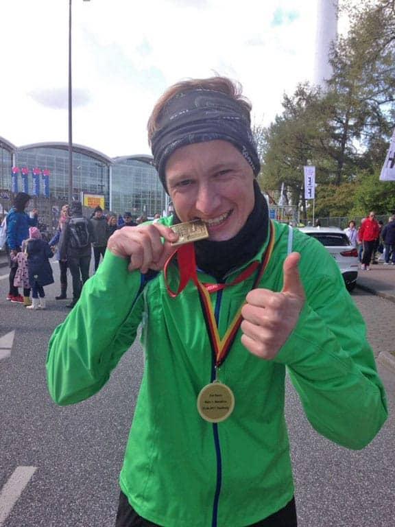 Kevin beißt auf seine Marathon Medaille