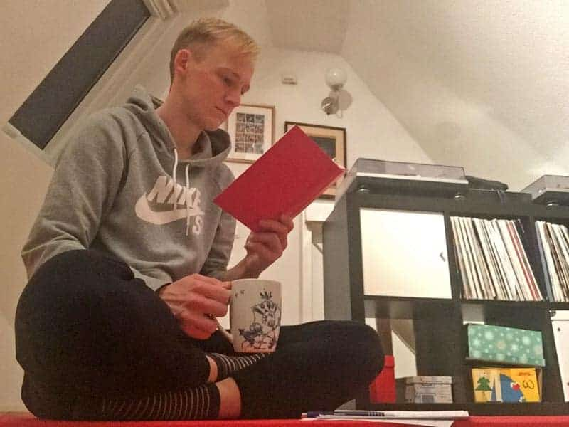 Kevin ließt beim Buch mit einer Tasse Kaffee in der Hand