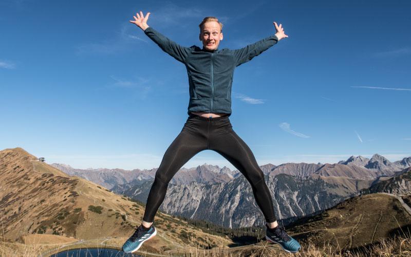 Lauftrainer Kevin von runnersflow springt in Laufklamotten im Gebirge in die Luft