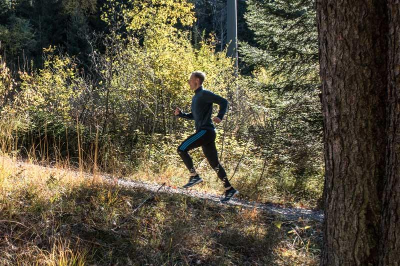 Ein Läufer joggt im Wald einen Berg hoch
