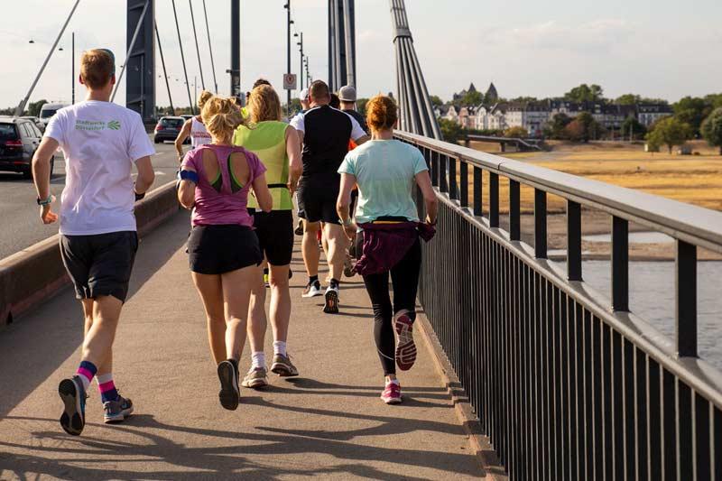 Eine Laufgruppe joggt auf einer Brücke