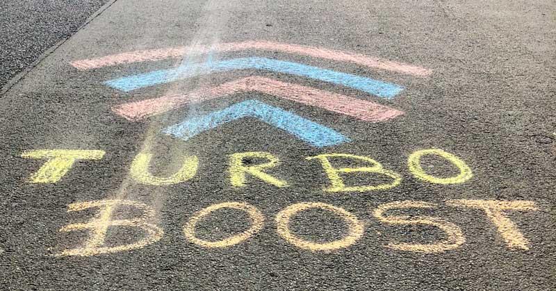 """Jemand hat auf eine Straße den Begriff """"Turbo Boost"""" gemalt"""