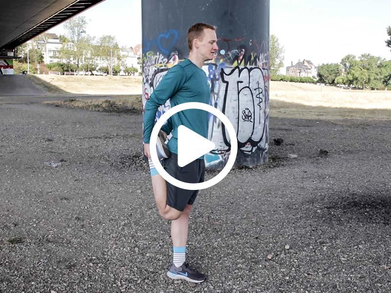 Lauftrainer Kevin zeigt eine Dehnübung für den vorderen Oberschenkel
