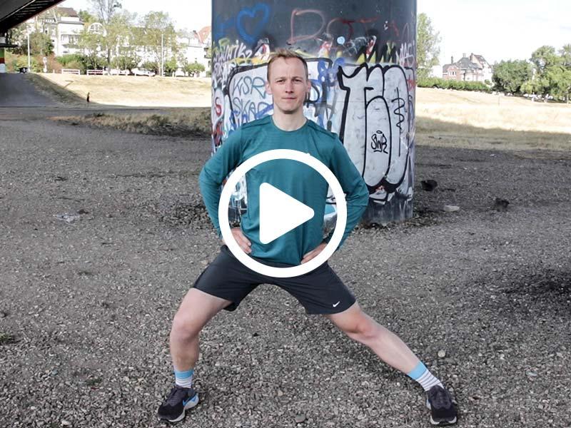 Lauftrainer Kevin zeigt eine Dehnübung für die Adduktoren