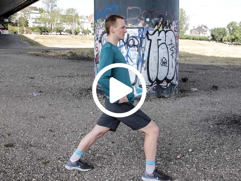Lauftrainer Kevin zeigt eine Dehnübung für die obere Wade