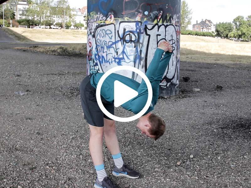 Lauftrainer Kevin zeigt eine Dehnübung für den Rückenstrecker