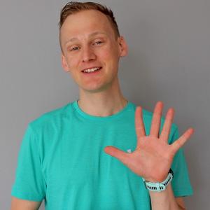 Lauftrainer Kevin zeigt mit den Fingern eine Fünf